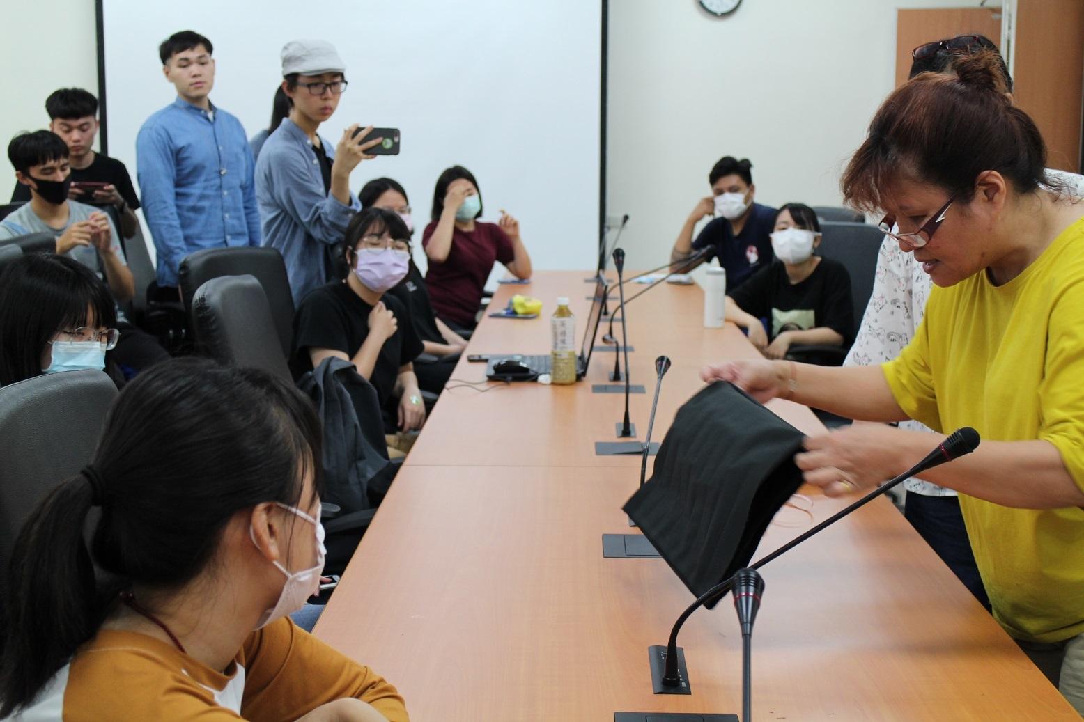 講師吳億樺(右方手持布料者)向同學說明布口罩套手縫方式