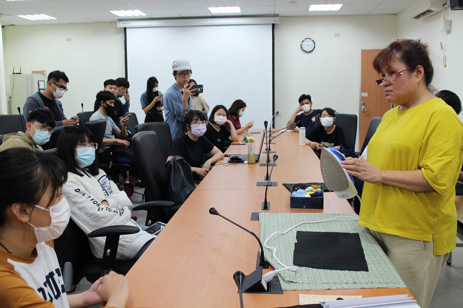 講師吳億樺(右方手持熨斗者)向同學說明熨燙布口罩套摺痕步驟
