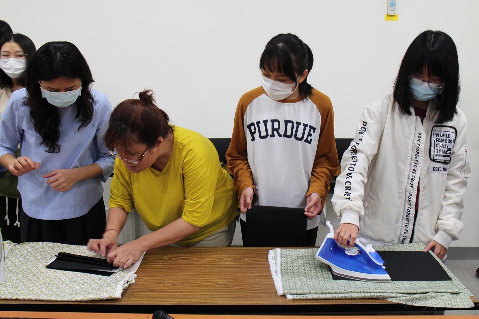 講師吳億樺(左二彎腰者)指導東華師生熨燙摺痕(左一為東華大學黃雅鴻老師)